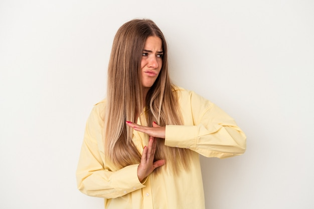 Young russian woman isolated on white background showing a timeout gesture.