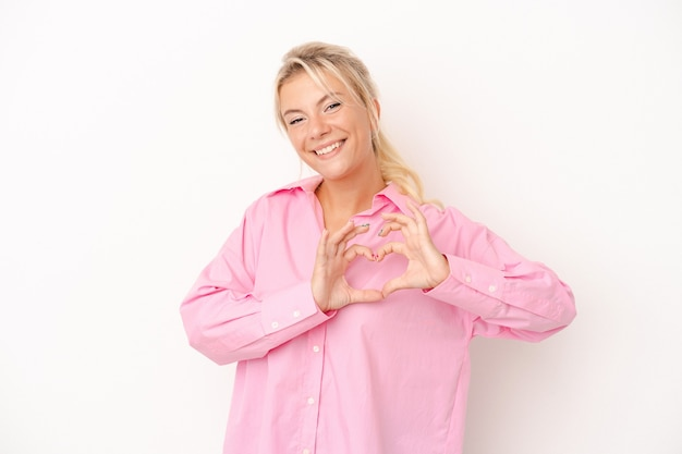 Young russian woman isolated on white background smiling and showing a heart shape with hands.