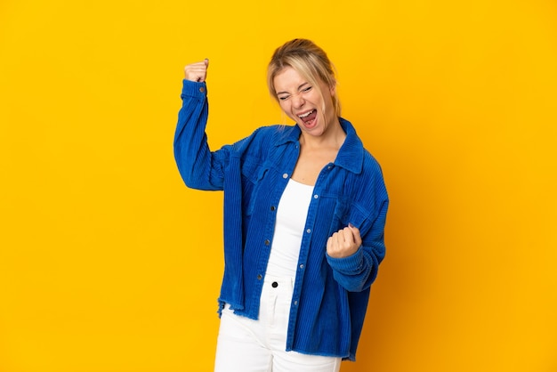 Young russian woman isolated on yellow background celebrating a victory
