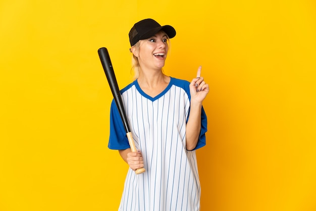 Young russian woman isolated on yellow background playing baseball and intending to realizes the solution while lifting a finger up