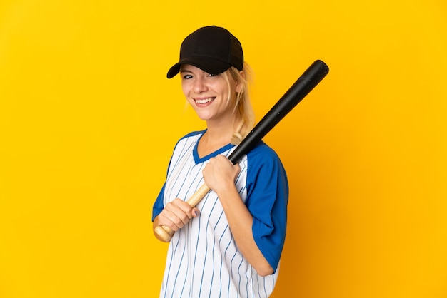 Young russian woman isolated on yellow background playing baseball