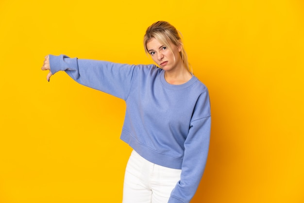 Young russian woman isolated on yellow background showing thumb down with negative expression
