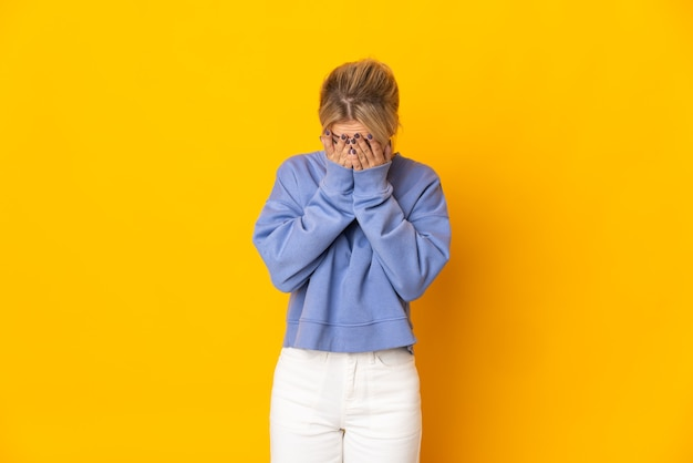 Young russian woman isolated on yellow background with tired and sick expression