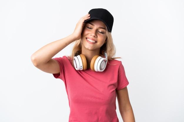 많이 웃 고 흰색 배경에 고립 된 젊은 러시아 여자 듣기 음악 프리미엄 사진
