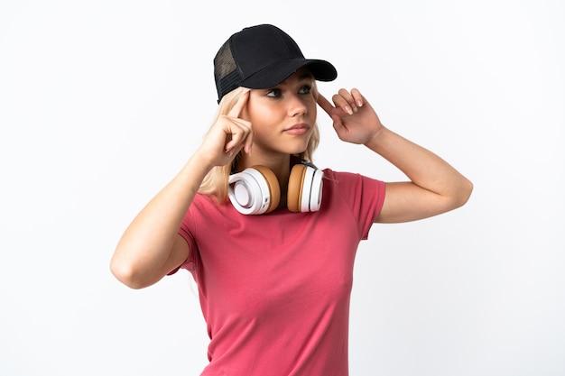 疑いと思考を持って白で隔離の音楽を聞いている若いロシアの女性