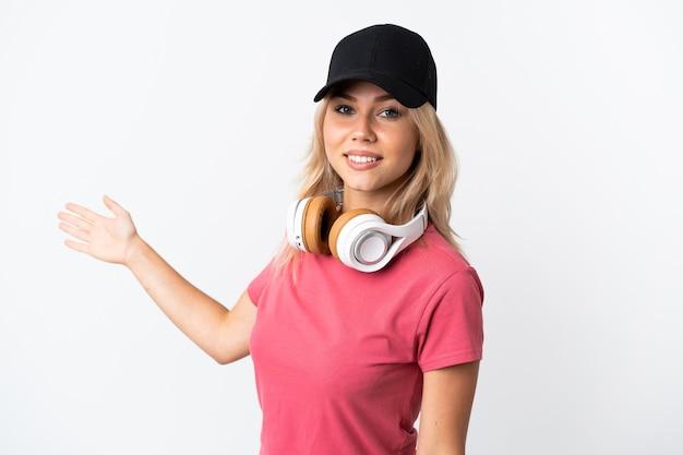 来るように誘うために手を横に伸ばして白い壁に隔離された音楽を聞いている若いロシアの女性
