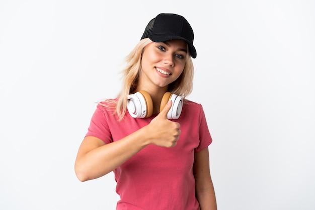 親指を立てるジェスチャーを与える白い壁で隔離の音楽を聞いている若いロシアの女性