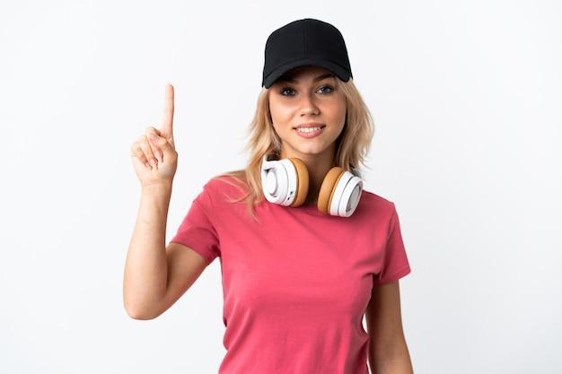 좋은 아이디어를 가리키는 흰 벽에 고립 된 젊은 러시아 여자 듣기 음악