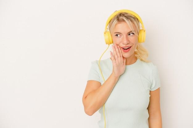 白い背景で隔離の音楽を聞いている若いロシアの女性は秘密の熱いブレーキングニュースを言って脇を見ています