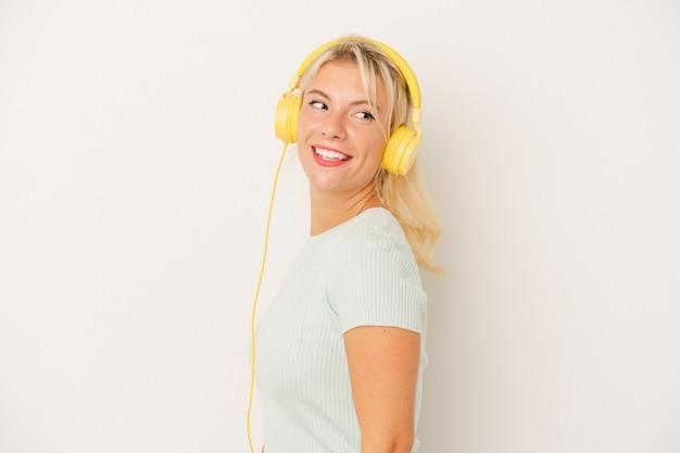 白い背景で隔離の音楽を聞いている若いロシアの女性は、笑顔、陽気で楽しい脇に見えます。