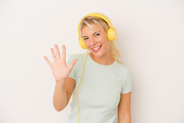 白い背景で隔離の音楽を聞いている若いロシアの女性は、指で5番を示して陽気に笑っています。