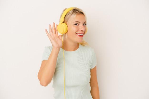 ゴシップを聴こうとしている白い背景で隔離の音楽を聞いている若いロシアの女性。