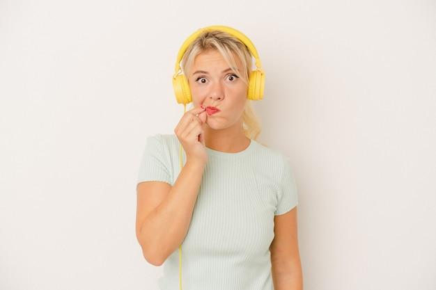 秘密を保持している唇に指で白い背景で隔離の音楽を聞いている若いロシアの女性。
