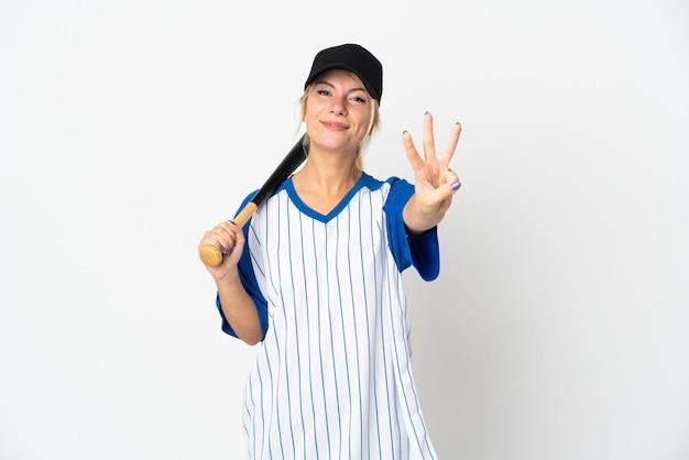 Молодая русская женщина играет в бейсбол на белом фоне счастлива и считает три пальцами