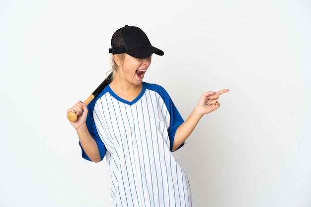 Young russian woman playing baseball isolated on white background pointing finger to the side and presenting a product
