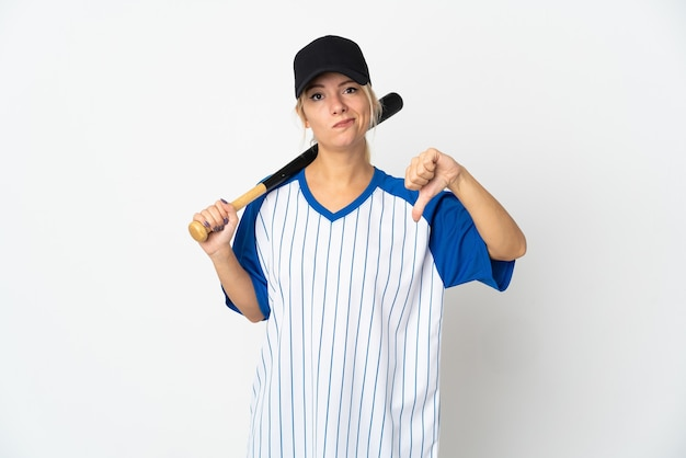 Young russian woman playing baseball isolated on white background showing thumb down with negative expression