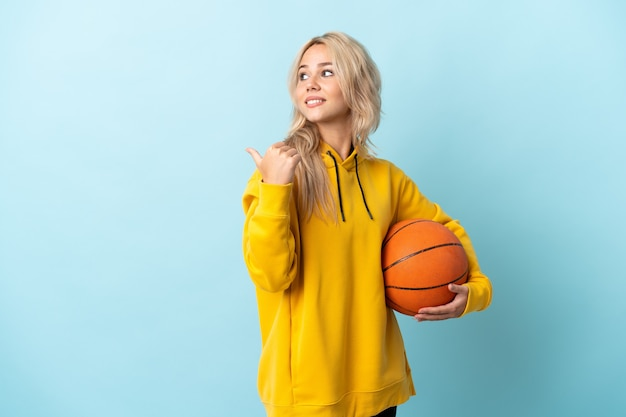 Young russian woman playing basketball isolated on blue background pointing to the side to present a product
