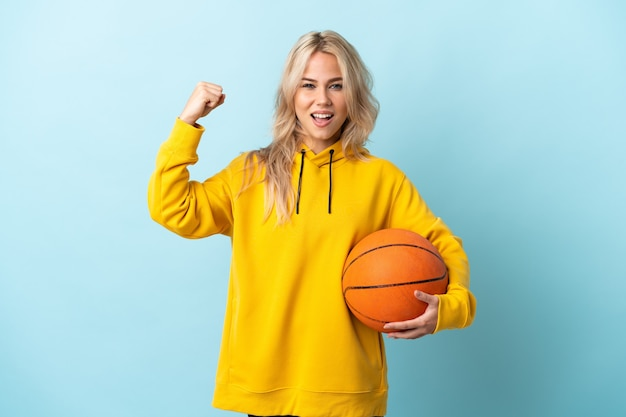 Young russian woman playing basketball isolated on blue celebrating a victory