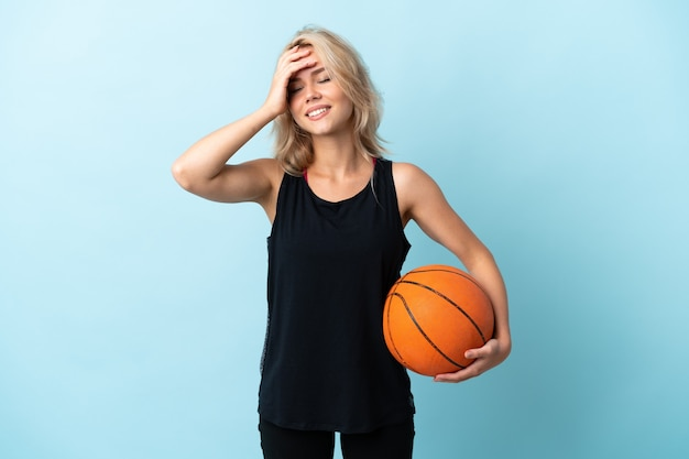 Young russian woman playing basketball isolated on blue smiling a lot