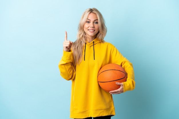 Young russian woman playing basketball isolated on blue wall pointing up a great idea