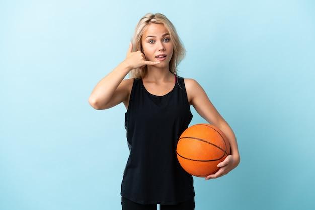 電話ジェスチャーを作る青い背景で隔離のバスケットボールをしている若いロシア人女性。コールバックサイン