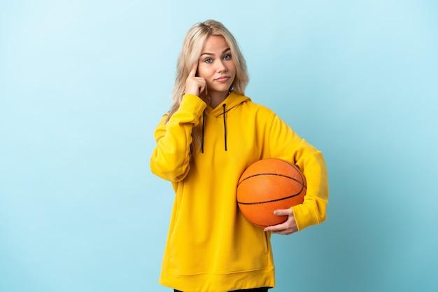 Молодая русская женщина играет в баскетбол изолирована на синем, думая об идее