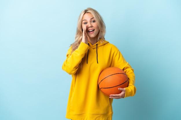 Молодая россиянка играет в баскетбол изолирована на синей стене и кричит с широко открытым ртом