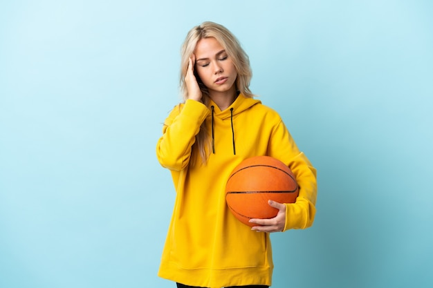 Молодая россиянка играет в баскетбол, изолирована на синей стене с головной болью