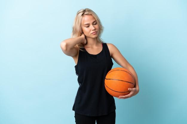 Молодая русская женщина играет в баскетбол изолирована на синем с шейной болью