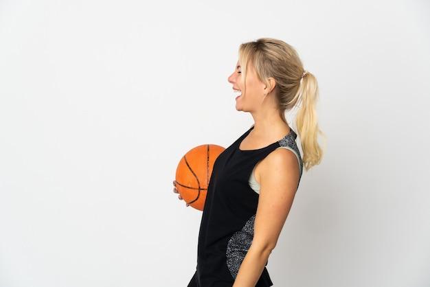 측면 위치에서 웃고 흰색 배경에 고립 농구 젊은 러시아 여자