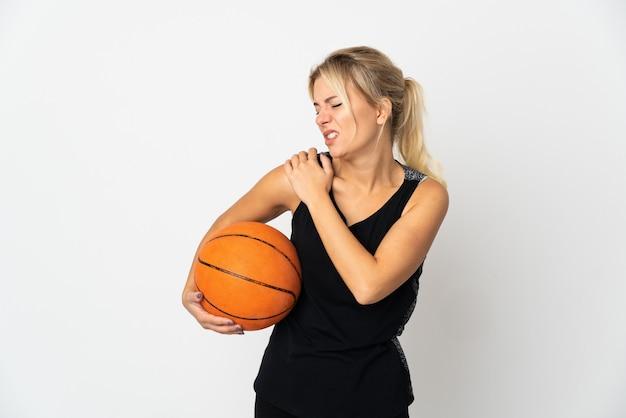 努力したために肩の痛みに苦しんでいる白で隔離のバスケットボールをしている若いロシアの女性