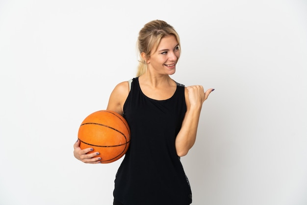 Young russian woman playing basketball isolated on white wall pointing to the side to present a product