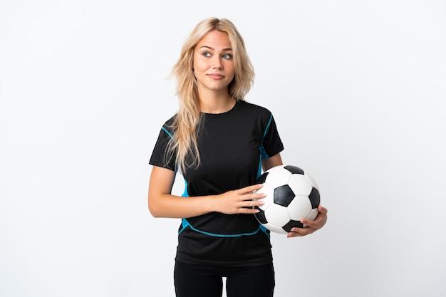 Молодая россиянка играет в футбол на белом фоне, сомневаясь, глядя в сторону