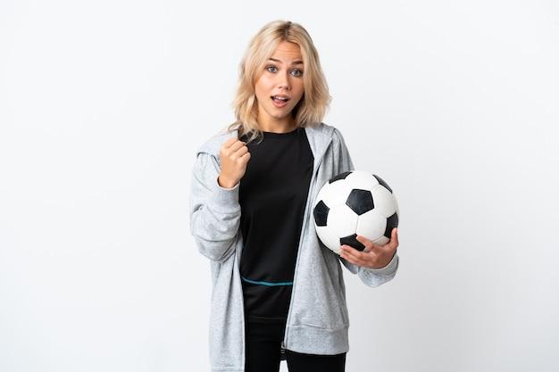 勝者の位置での勝利を祝って白で隔離のサッカーをしている若いロシアの女性