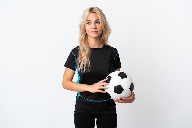 Молодая россиянка играет в футбол, изолированные на белом, делая жест сомнения, глядя в сторону