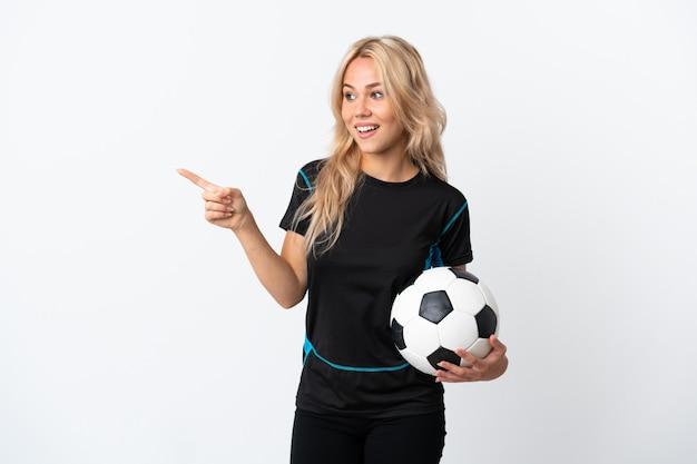 Молодая россиянка играет в футбол, изолирована на белом, указывая пальцем в сторону и представляет продукт