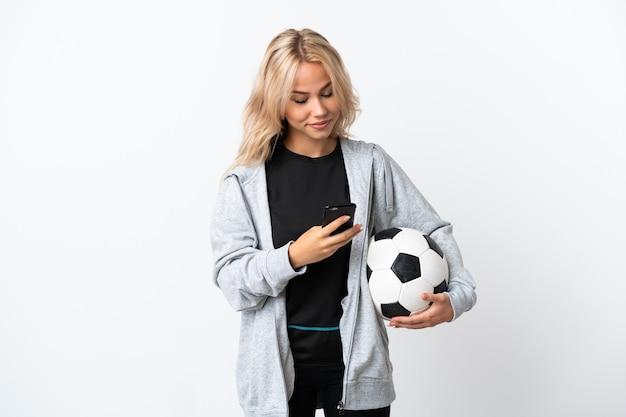 Молодая россиянка играет в футбол изолирована на белом, отправляя сообщение с мобильного телефона