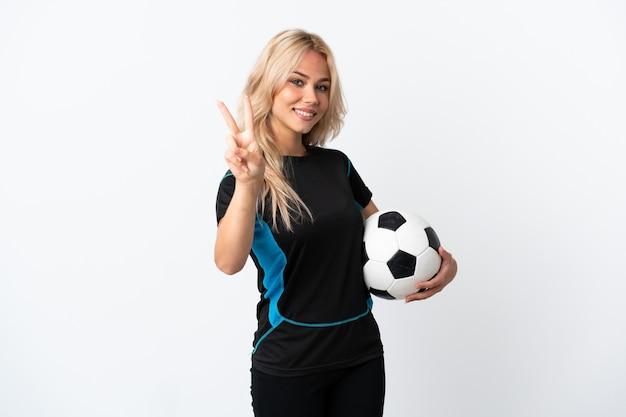 Молодая русская женщина играет в футбол, изолированную на белом, улыбается и показывает знак победы