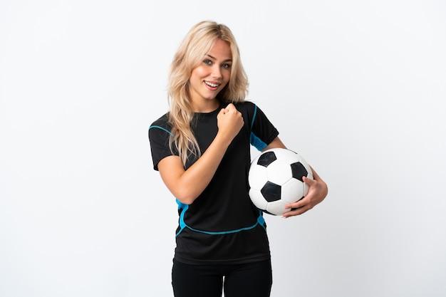 勝利を祝って白い壁に孤立したサッカーをしている若いロシアの女性