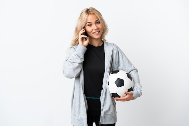 Молодая русская женщина играет в футбол изолирована на белой стене, разговаривая с кем-то по мобильному телефону