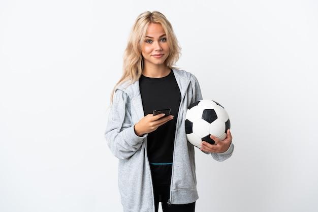 Молодая россиянка играет в футбол изолирована на белой стене, отправляя сообщение с мобильного телефона