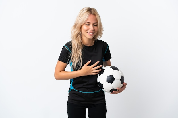 たくさん笑って白い壁に孤立したサッカーをしている若いロシアの女性