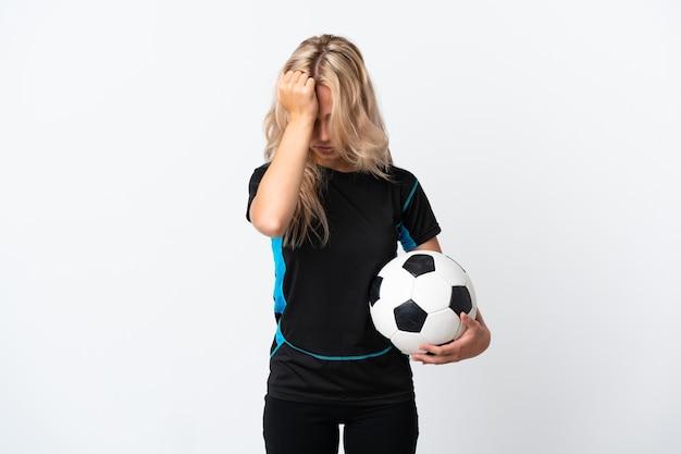 Молодая русская женщина играет в футбол изолирована на белой стене с головной болью