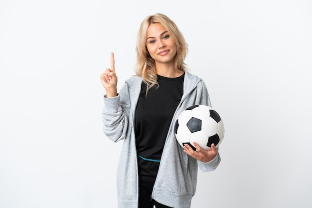 Young russian woman playing football isolated on white wall showing and lifting a finger in sign of the best