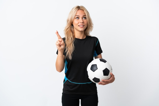 Young russian woman playing football isolated on white wall with fingers crossing and wishing the best