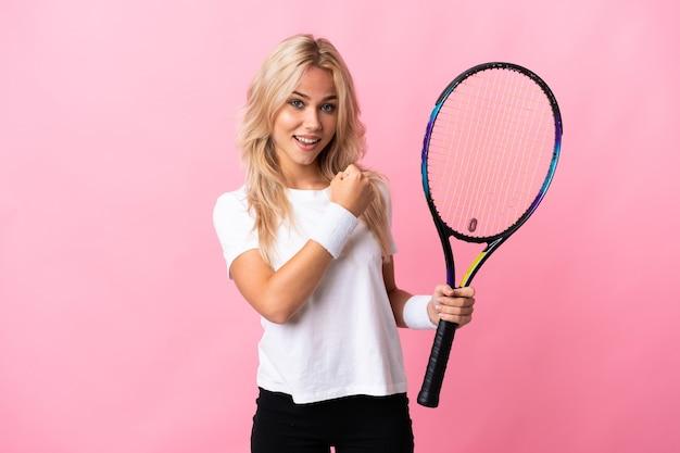 Молодая россиянка играет в теннис на фиолетовом фоне празднует победу