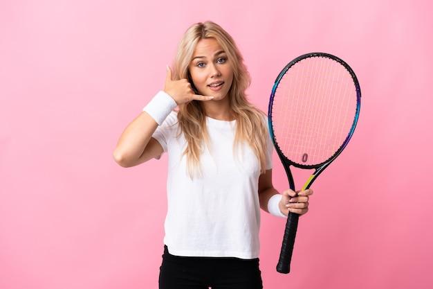Молодая русская женщина играет в теннис на фиолетовом фоне, делая жест телефона. перезвони мне знак