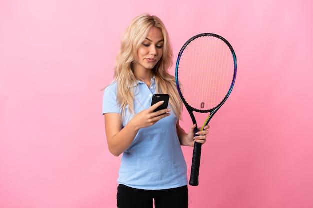 Молодая русская женщина играет в теннис на фиолетовом фоне, думая и отправляя сообщение