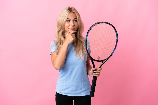 Молодая русская женщина, играющая в теннис, изолирована на фиолетовом, думая об идее, глядя вверх