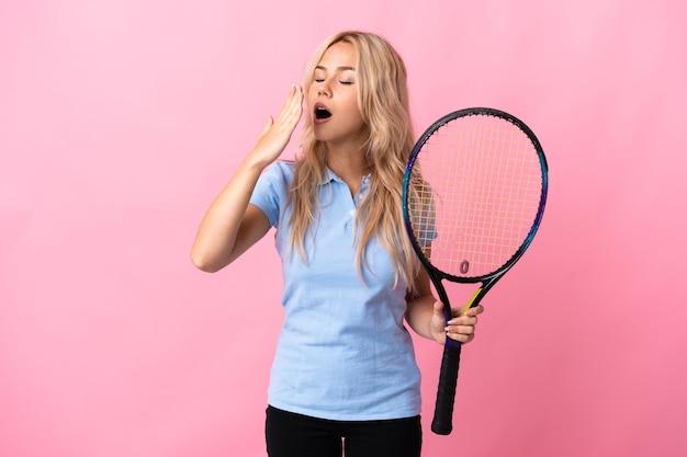 Молодая русская женщина, играющая в теннис, изолирована на фиолетовой стене, зевая и прикрывая широко открытый рот рукой